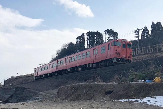 富山県高岡市、雨晴海岸の女岩近くで見るJR氷見線