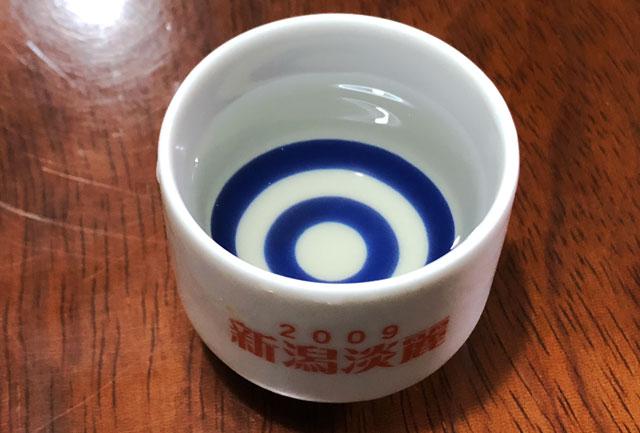 越中八尾の酒蔵「玉旭酒造」の日本酒「富富富(ふふふ)」の色味を斜めから見たところ