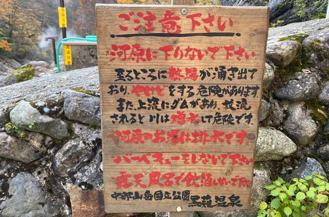富山県黒部市宇奈月町の秘湯黒薙温泉の混浴大露天風呂 源泉(いずみ)の注意看板